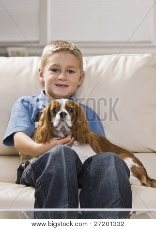 A cute little boy holding a dog on his lap.  He is smiling.  Vertically framed shot.