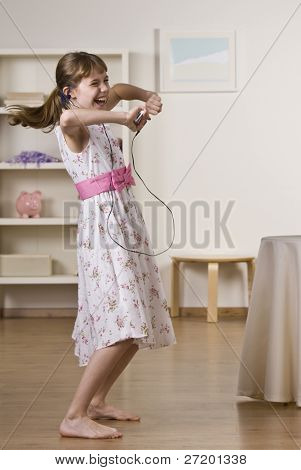 A happy little girl dancing to music.  She is listening to headphones from an Mp3 player.  Vertically framed shot.