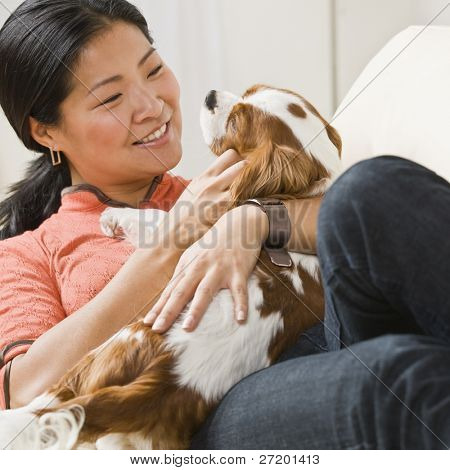 Smiling Asian woman with puppy on her lap. Square.