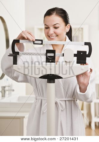 Smiling brunette weighing herself and smiling. Vertical