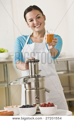 A woman is standing in her kitchen holding out a cup of juice.  She is smiling at the camera.  Vertically framed shot.