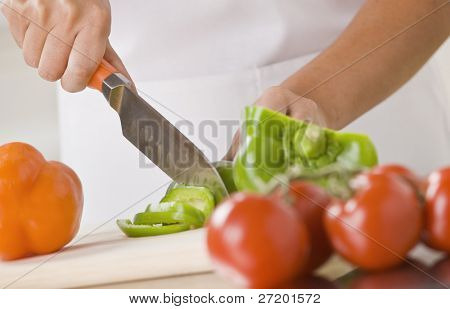 A woman is slicing produce in a kitchen.  Horizontally framed shot.