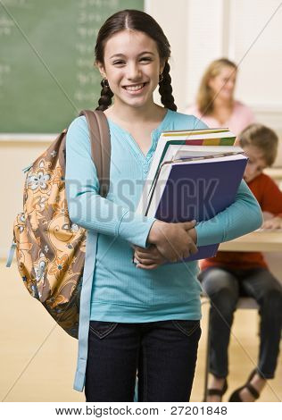 Student carrying backpack and books