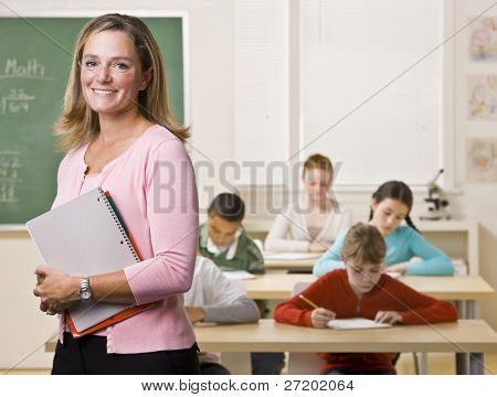 Teacher standing with notebook in classroom