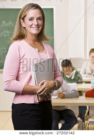 Teacher standing with notebook in classroom