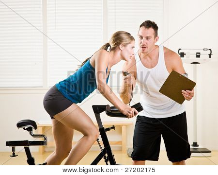 Trainer timing woman on stationary bicycle