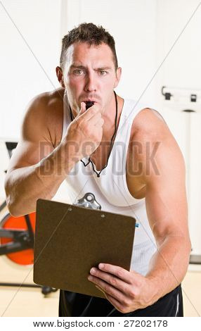 Personal trainer blowing whistle in health club