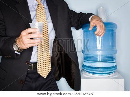 Businessman drinking water from water cooler