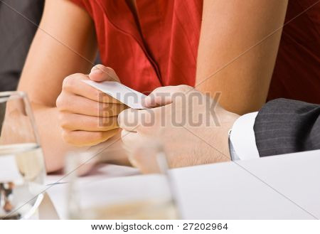 Businesswoman handing co-worker her business card