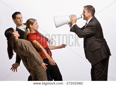 Businessman shouting at co-workers with megaphone