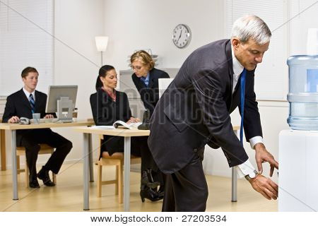 Businessman getting water from water cooler