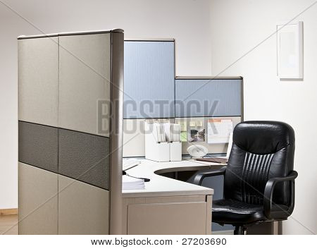 Empty chair at desk in cubicle