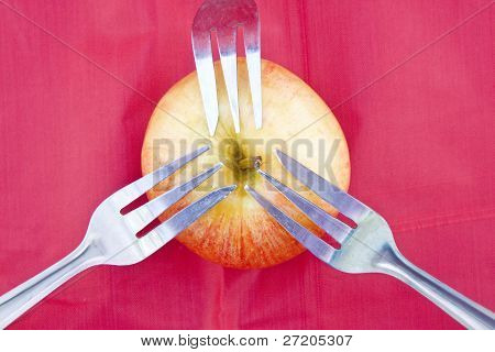 Red Apple On Red With Three Forks