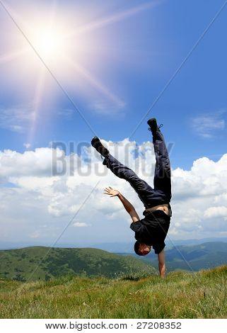 Homem feliz nas montanhas permanecer cabeça sobre saltos por lado