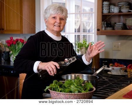 Mature Woman Sautes Vegetables.