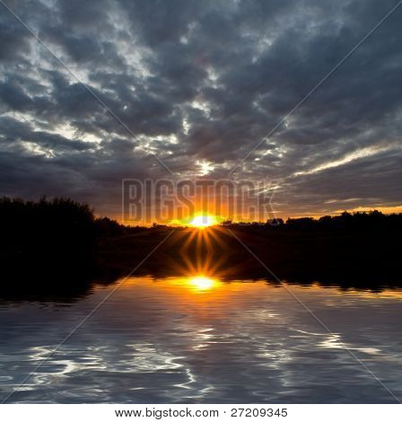 Nice sunset and lead clouds with water reflection