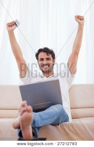Portrait of a cheerful man buying online in his living room