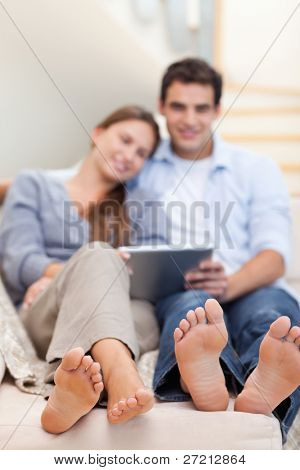 Portrait of a lovely couple using a tablet computer in their living room