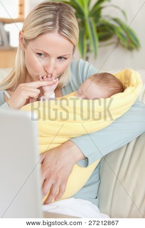 Young mother kissing her baby's hand while looking at the laptop