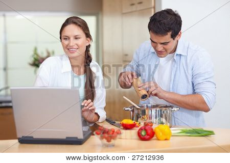 Pareja joven con un cuaderno para cocinar en su cocina