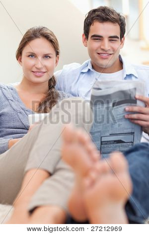 Portrait of a couple reading a newspaper in the morning in their living room