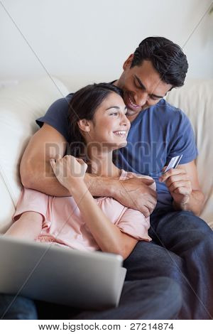 Portrait of a lovely couple booking their holidays online in their living room