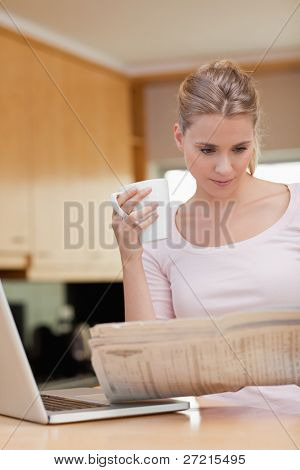Portrait of a woman reading the news while having coffee in her kitchen