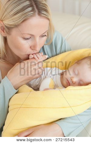 Close up of young mother kissing her baby's hand