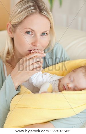 Close up of affectionate young mother kissing her baby's hand