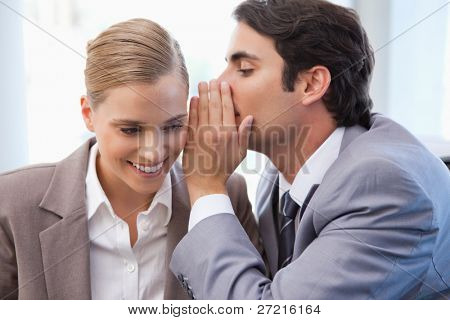 Businessman whispering something to his colleague in a meeting room