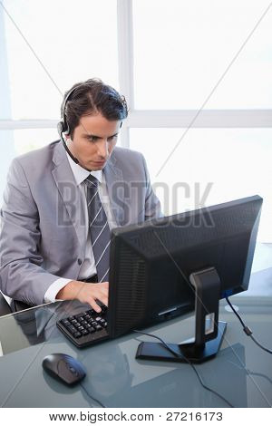 Portrait of a sales assistant working with a monitor in his office