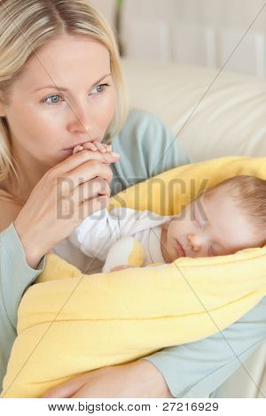 Close up of provident young mother kissing her baby's hand