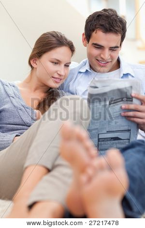 Portrait of a couple reading a newspaper while lying on a couch in their living room