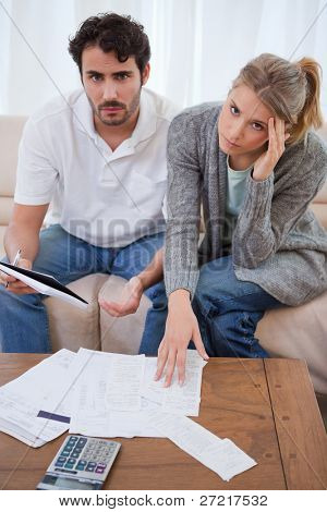 Portrait of a worried young couple looking at their bills in their living room