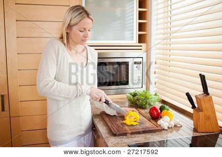 Side view of woman slicing yellow bell pepper