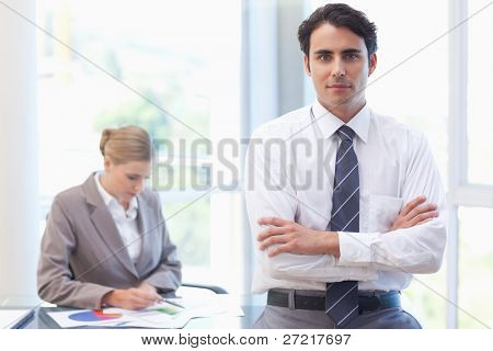 Businessman posing while his colleague is working in a meeting room