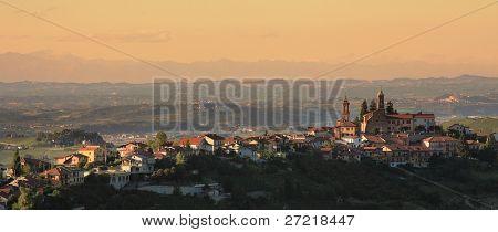 Vista panorámica sobre la ciudad en la colina al atardecer en Piamonte, norte de Italia.