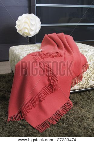 Blanket draped over an ottoman