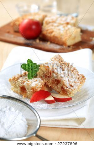 Homemade apple pie, mint leafs, colander with icing sugar