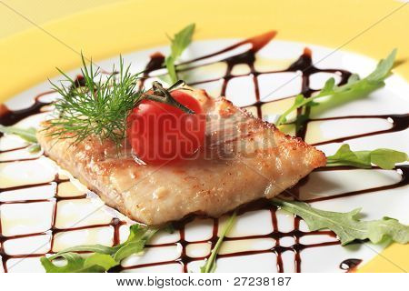 Salmon trout fillet garnished with arugula and balsamic reduction