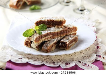 Two colored honey ginger-cake pieces on a plate spinkled with icing sugar decorated with mint leafs on a top of a pile