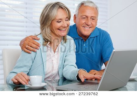 Mature woman having tea and browsing internet with her husband on laptop