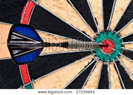 A dart pierces the bullseye of a dart board