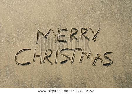 A message inscribed in the wet sand along a beach shoreline wishing you a Merry Christmas.