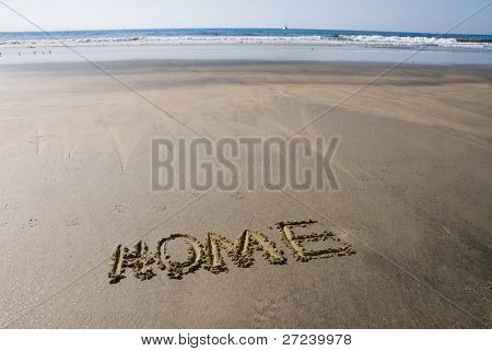 A message inscribed in the wet sand along a beach shoreline depicting home.