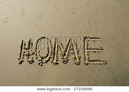 A message inscribed in the wet sand along a beach shoreline depicting home