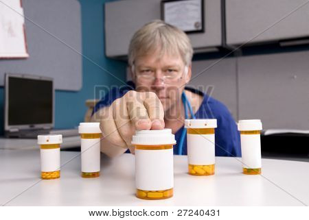 A doctor selects a medication for his customer.  Labels are blank to allow for copy to be placed on the pill bottles.