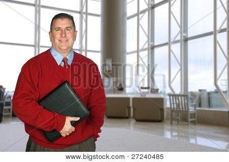 A businessman stands with his leather folder in a large lobby waiting for a meeting