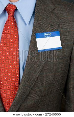 Un empresario con una etiqueta de nombre en blanco y un traje de negocios fuerte.