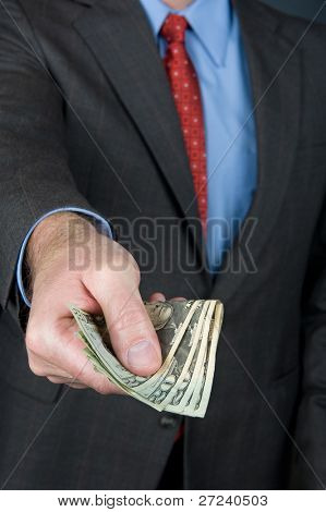 A businessman extending a wad of cash as if offering a payoff or paying for goods.